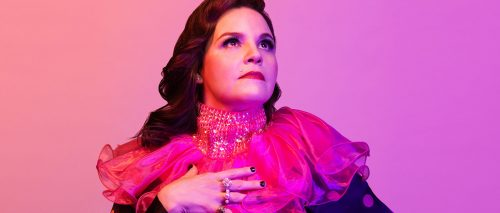 Image info: photo of Michaela Washburn by Tanja-Tiziana. Pink background, performer with pink and sequined neck ruffle looking off into distance