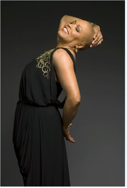 Image info: Dee Dee Bridgewater. Photo by-Mark-Higashino. Woman dressed in black, smiling, with arm holding head leaning back