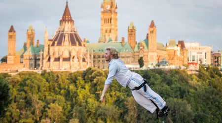 Creations in Vivo artist performing on high sway poles with a view of Ottawa Parliament in the background.