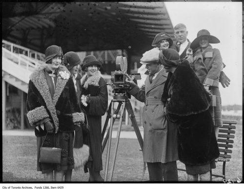 Cinematographer Willard van Enger with women around camera at Woodbine race track