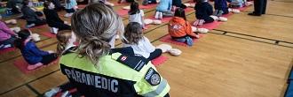 A paramedic leads children through a first aid course in a gymnasium