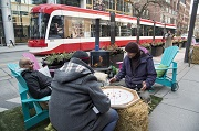 Three men sit around a board game on King Street with a streecar passing by.