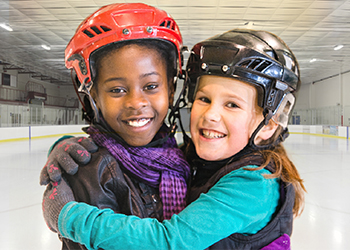 Two children hug on an ice rink while wearing hockey helmets.