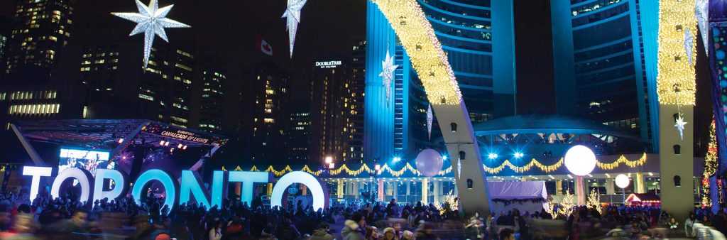 Nathan Phillips Square skating rink at night with Toronto Sign and arches glittering with lights.