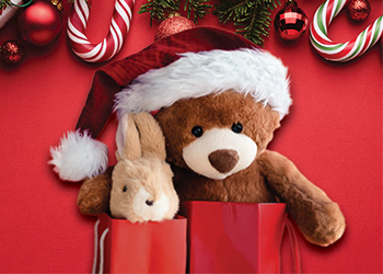Teddy bear and stuffed toy rabbit in red gift bags with candy canes and holly.