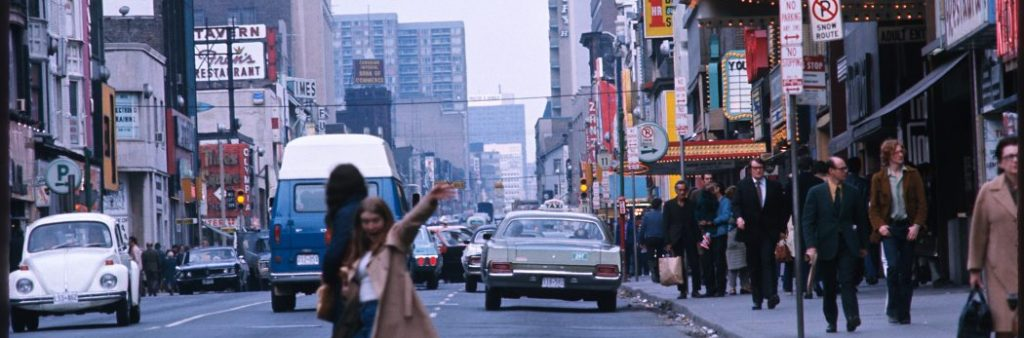 Two people crossing Yonge Street in the summer of 1979, with many cars and people on the street