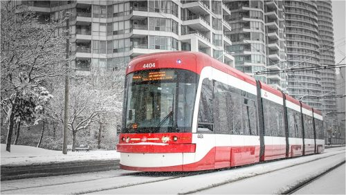 New red Toronto streetcar in snow. High rises in background.