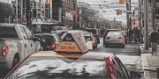 Photo of cars, including a taxi, at a red light stop on Spadina Avenue.