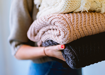 Person holding three large knit sweaters.