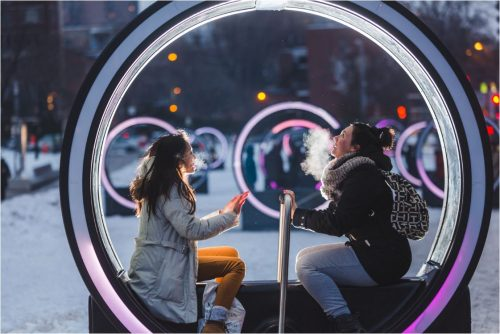 Image info: Loop. Photo Ulysse Lemerise. OSA Images. two people in large lighted circle with handle for moving it.