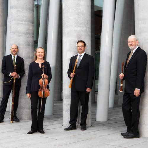4 musicians holding their instruments standing in front of grey columns