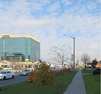 Photo of Finch Ave facing East with traffic heading west, with sidewalks and a mid-rise office building with retail on the ground floor.