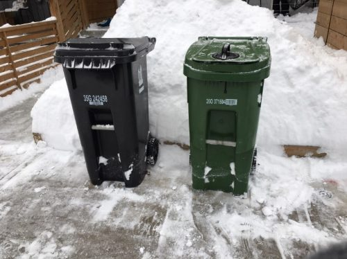 Black Bin and Green Bin placed two feet apart in front of a snow bank.