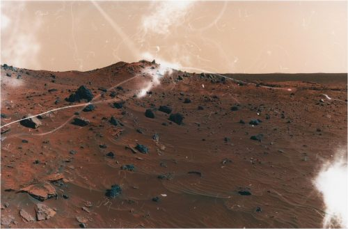 Barren Mars-like landscape with rocks and reddish sand.