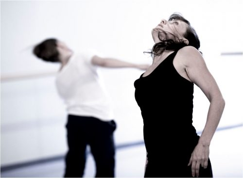 2 dancers - foreground in black with head tipped back; background in white, head tipped to side