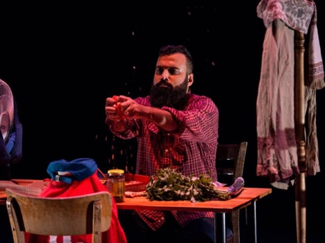 Scene from Suitcase/Adrenaline. Performer sitting at table dropping crumbs from hands.