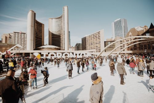 Crowd skating at Nathan Phillips Square rink during the day.