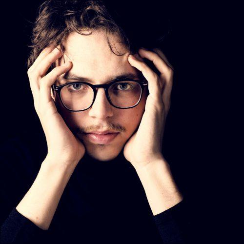 Lucas Debargue starring at camera - closeup of face and hands