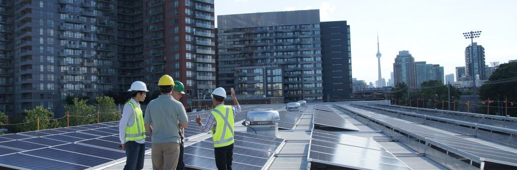 An image of four City of Toronto workers in hardhats on a building roof with rows solar PV panels. The CN Tower can be screen on the horizon