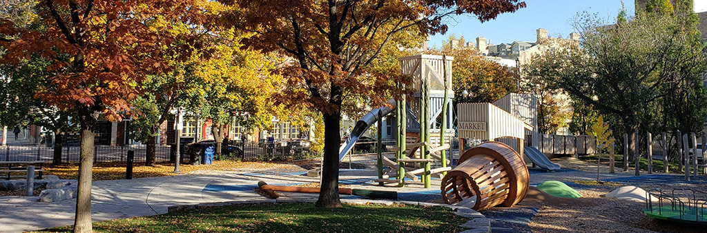 The playground in fall. The main structure includes climbing equipment and a slide.