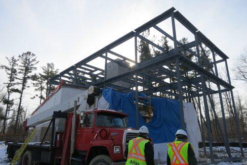 construction of building exterior showing steel beams, truck and two construction workersxterior walls, steel beams, cinder-block walls