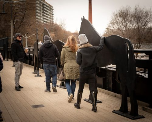 image of people walking across the Kay Gardner Beltline Park Bridge touching the public art installation of horses made out of iron