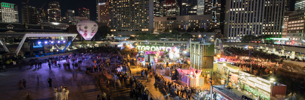 Fair and market at Nathan Phillips Square at night with Toronto Sign in the background.