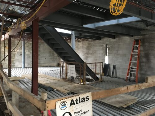 Exposed metal deck of 2nd floor in progress, fall protection barriers, existing concrete block exterior walls and steel exit stair extending between 3rd floor and 2nd floor