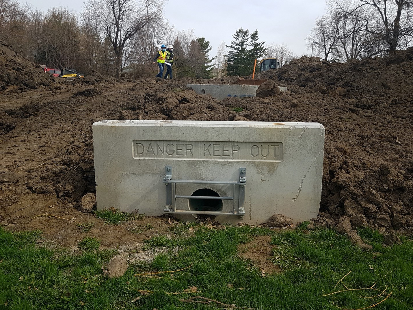 A new culvert and headwall has been installed to channel stormwater to a catchbasin.