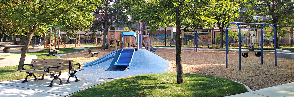 An image of the new Art Eggleton Park Playground after construction. New concrete pathways with benches and trees are in the foreground surrounding the new playground with various play features and components in the background.