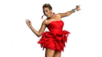 Portrait of Shakura S'Aida dancing in a red dress against white background.