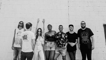 Black and white photo of July Talk with James Baley and Kyla Charter against white brick wall.