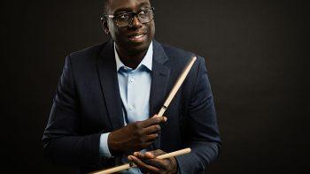 Portrait of Larnell Lewis holding drum sticks, against black background.
