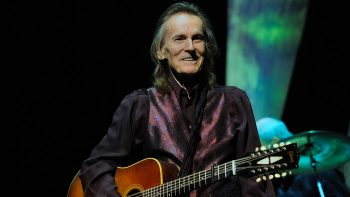 Portrait of a Canadian folk artist Gordon Lightfoot on stage with an acoustic guitar in his hand.