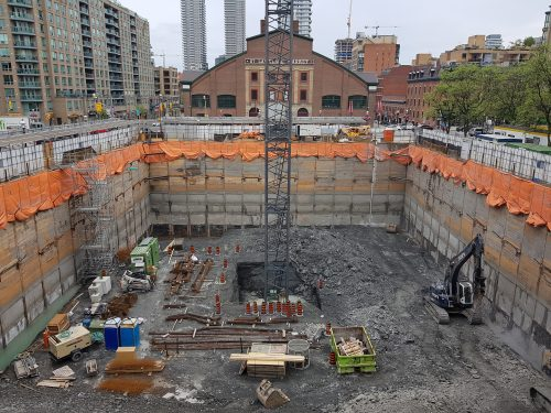 excavation and shoring nearing completion, tower crane installation underway
