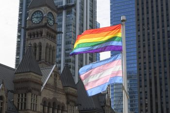 Pride and Transgender flags flying on the podium rooftop at City Hall