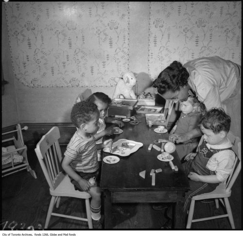 Children seated around table eating, at nursery, with teacher