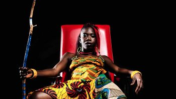 Portrait of d'bi.young anitafrika sitting on a red chair