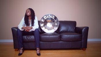 Joy Lapse sitting on a black leather sofa next to a steelpan