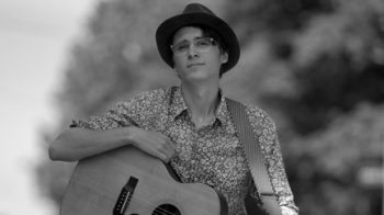 Black and white portrait of Mather Magneson in a hat holding an acoustic guitar.