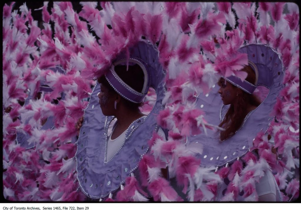 Two women in wearing costumes made of pink feathers fro Caribana carnival