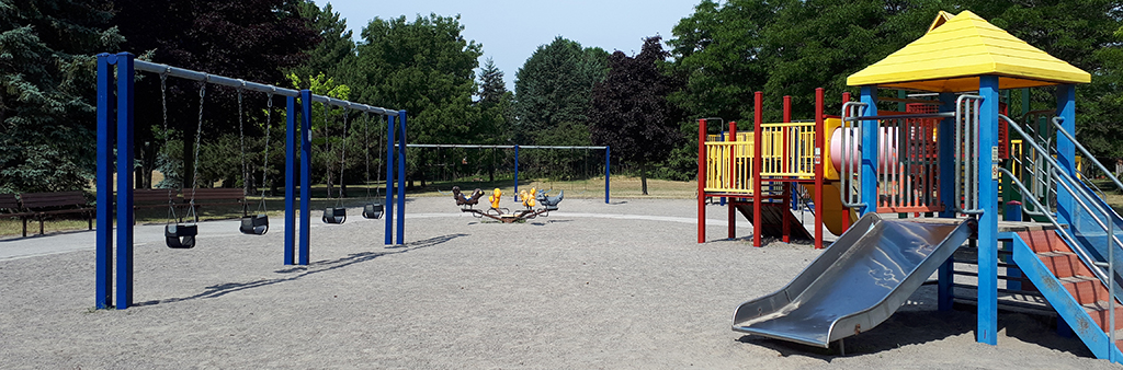 Highland Creek Community Park's playground, featuring swings, climbing equipment and slide.