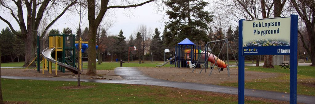 A playground srrounded by trees and a pathway, featuring swings, climbing equipment and slide.