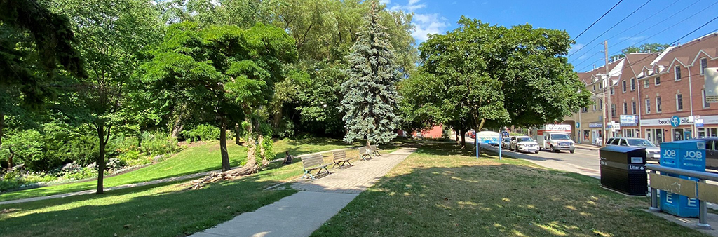 A sidewalk running along Ivan Forrest Gardens, with a few benches and trees.