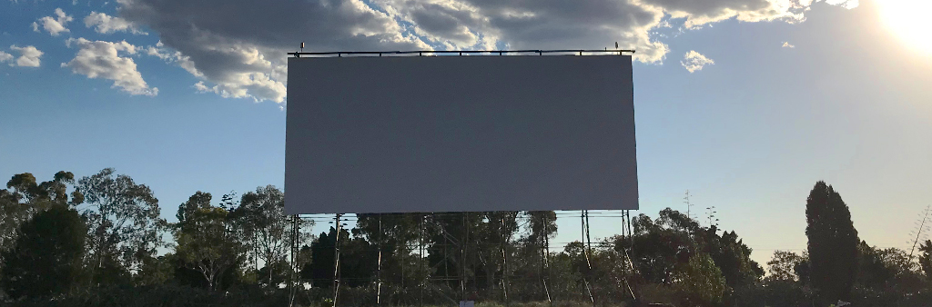 Blank outdoor drive-in movie screen in the daylight with trees in background.