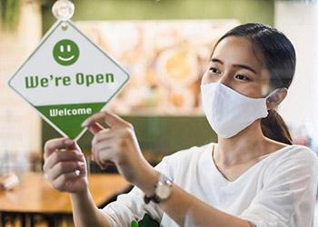 woman in mask hangs We're Open sign in window