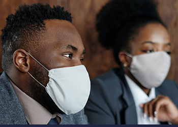 Man and woman wearing masks indoors