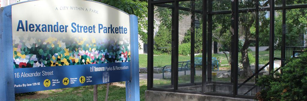Alexander Street Parkette's sign, near an all glass structure.