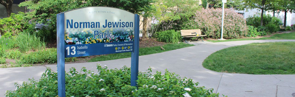 The sign for Normal Jewison Park, which is situated in a garden near a pathway. A bench is in the background.