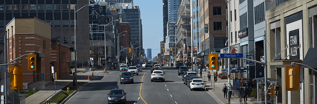 A photo of Yonge Street near Merton Street looking north, showing traffic, pedestrians, and mixed-use development along the street.